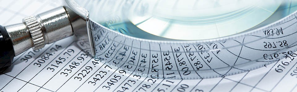 Magnifying glass over financial reports. Lindquist works with businesses to prevent and detect fraud.
