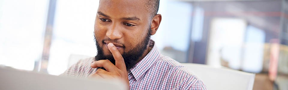 Man at computer contemplating strategies to boost 401(k) participation.