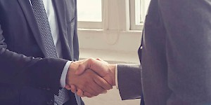 Two men in suits shaking hands. Best practices in payroll compliance programs: employer outreach programs.