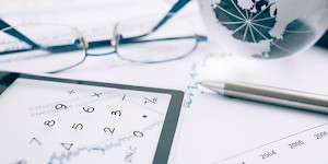 Calculator, glasses and a pen on a table. Transitions within an organization inherently create the potential for fraud.  Lindquist helps businesses protect themselves against fraud.